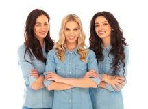 站立用手的三名确信的偶然妇女横渡 免版税库存图片