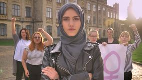 站立用横渡的手的hijab的美丽的白种人女性在街道上的男女平等主义者示范中间 股票录像
