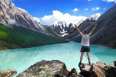 站立用被举的手在美丽的山湖附近和享受谷视图的远足者 免版税库存照片
