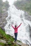 站立用被举的手的女孩在瀑布 图库摄影