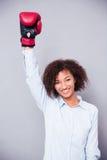 站立用被举的手的妇女在拳击手套 免版税库存图片