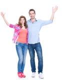 站立用被举的手的微笑的夫妇。 库存图片