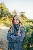 站立用被折叠的手的牛仔布夹克的美丽的年轻白肤金发的妇女室外 图库摄影