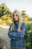 站立用被折叠的手的牛仔布夹克的美丽的年轻白肤金发的妇女室外 库存图片