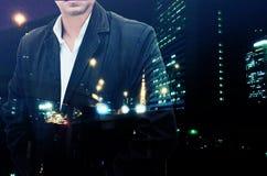 站立用他的在口袋的手的一个确信的有胡子的商人的画象躺在了夜城市风景背景 双重e 免版税库存照片