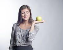 站立用绿色苹果的年轻美丽的妇女在手上 库存照片