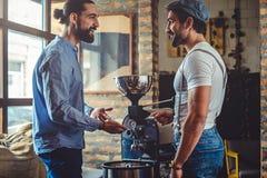 站立男性的所有者愉快由咖啡烘烤器 免版税库存图片