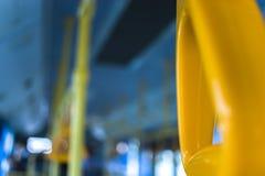 站立的乘客的黄色垂悬的把柄在一辆现代公共汽车上 郊区和都市交通 免版税库存图片