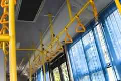 站立的乘客的黄色垂悬的把柄在一辆现代公共汽车上 郊区和都市交通 库存照片