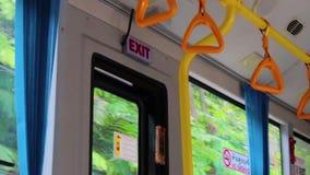 站立的乘客的黄色垂悬的把柄在一辆现代公共汽车上 郊区和都市交通 股票录像