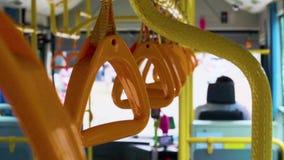 站立的乘客的黄色垂悬的把柄在一辆现代公共汽车上 郊区和都市交通 影视素材