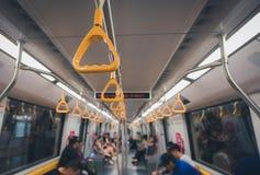 站立的乘客的黄色扶手栏杆地铁的 免版税库存照片
