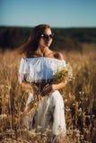 站立的太阳镜的性感的年轻女人摆在草甸 免版税库存照片