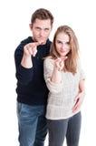 站立的夫妇显示观看您打手势 免版税库存照片