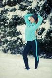 站立的女孩佩带的冬天运动服,树背景 免版税图库摄影