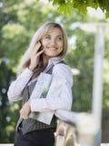 站立的女实业家室外与手机和工商业票据 免版税库存照片