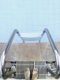 站立的某人去与梯子的游泳,镀铬物口气 库存照片