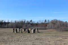 站立的石头圈子类似巨石阵,但是位于小农村社区华莱士新斯科舍春天 免版税库存图片
