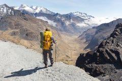 站立的背包徒步旅行者远足旅游山边缘足迹,玻利维亚 免版税库存图片