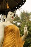 站立的菩萨雕象在泰国寺庙的一把伞下 免版税图库摄影