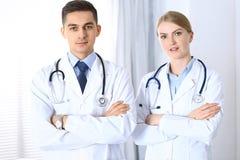 站立直接与胳膊的医生在医院横渡了 准备好的医师帮助 医疗保健,配合的概念和 免版税库存图片