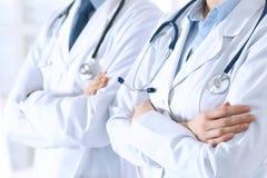 站立直接与胳膊的未知的医生队在医院横渡了 准备好的医师帮助 医疗保健,保险 库存图片