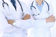 站立直接与胳膊的未知的医生队在医院横渡了 准备好的医师帮助 医疗保健,保险 图库摄影