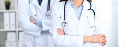 站立直接在医院办公室的未知的医生Groupe  关闭听诊器在实习者乳房 免版税库存图片
