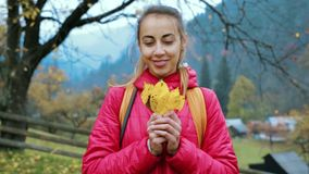 站立红色的夹克的俏丽的微笑的妇女户外,在手上拿着一些片干燥黄色与他们的叶子和戏剧 影视素材