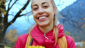 站立红色的夹克的俏丽的微笑的妇女户外,在手上拿着一些片干燥黄色与他们的叶子和戏剧 股票录像