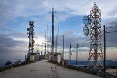 站立网络塔的系列高在除一个沙滩以外的峭壁附近 数十导线连接到每传输给 图库摄影