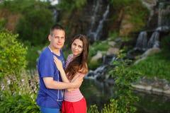 站立美好的夫妇拥抱在自然的日落在瀑布附近 免版税库存图片