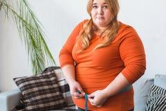 站立胖的妇女的体育在家对卷尺负不快乐 免版税库存图片