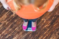 站立胖的妇女的体育在家看标度顶视图特写镜头 免版税库存照片