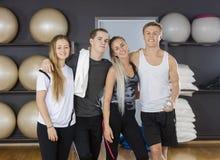 站立胳膊的男性和女性朋友在健身房 免版税库存图片