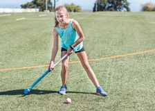 站立运动的女孩看准备好的照相机使击中曲棍球球 库存照片