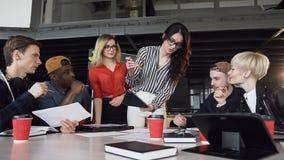 站立近在桌附近和给方向的创造性的女性组长在见面的年轻创造性的队在办公室 股票录像