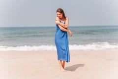站立近在蓝色礼服的海滩旁边的美丽的女孩 库存照片