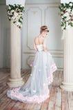 站立近的专栏的一件紫色礼服的可爱的妇女 方式 免版税库存图片