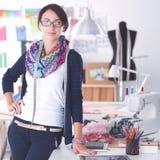 站立近的书桌的美丽的时装设计师在演播室 库存图片