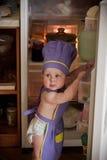 站立近的冰箱的一个首要帽子的小男孩 库存照片