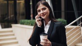 站立近的办公室中心的快乐的年轻女商人,谈话在智能手机 调查照相机的她 股票录像