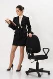 站立近的办公室椅子的女商人 免版税库存图片