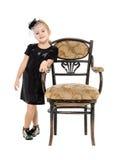 站立近的古色古香的椅子的小女孩 免版税图库摄影