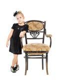 站立近的古色古香的椅子的小女孩 图库摄影