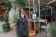 站立近的咖啡馆的美丽的女孩 免版税图库摄影