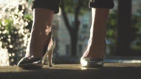 站立近的喷泉的典雅的银色鞋子的妇女 股票录像