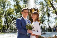 站立近的喷泉的新娘和新郎室外射击在公园 免版税图库摄影