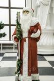 站立近的圣诞树的传统圣诞老人装饰了新年好和圣诞节 免版税库存照片