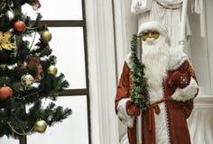 站立近的圣诞树的传统圣诞老人装饰了新年好和圣诞节 免版税库存图片